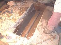 浄化槽の側面の約2/3を切って下穴をあけて砂を埋戻し配管